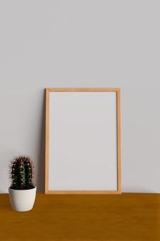 Maquette cadre sur table avec cactus.
