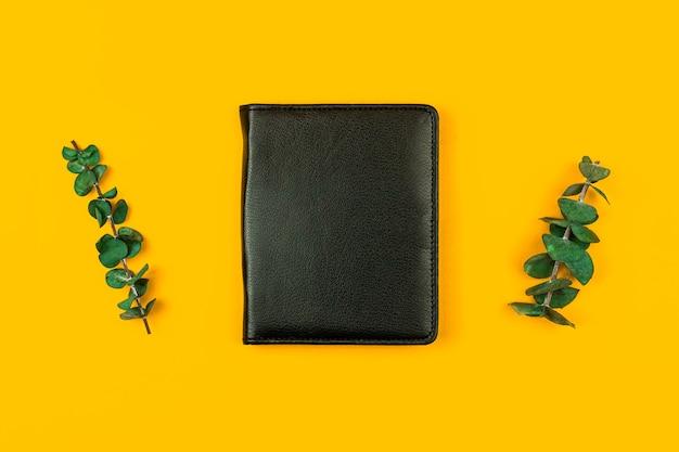 Maquette de cahier en cuir noir avec fleurs séchées, concept de bureau et d'espace de travail, fond jaune, photo à plat et vue de dessus