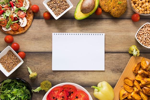 Maquette de cahier entourée de nourriture végétalienne