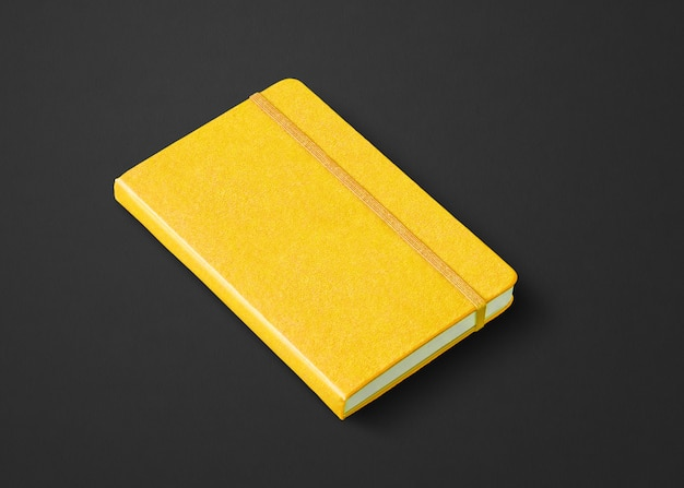 Maquette de cahier fermé jaune isolé sur noir