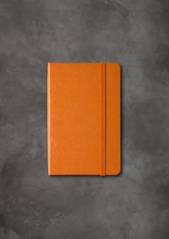 Maquette de cahier fermé orange isolé sur béton foncé