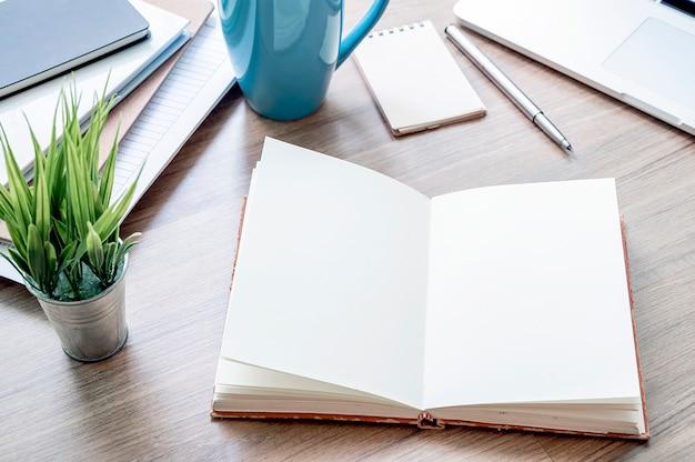 Maquette cahier ouvert avec une page blanche, un ordinateur portable et des fournitures sur une table en bois.
