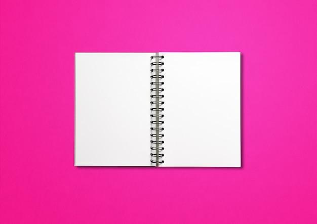 Maquette de cahier à spirale ouverte vierge isolée sur fond rose