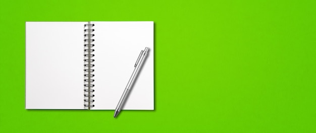 Maquette de cahier à spirale ouverte vierge et stylo isolé sur vert