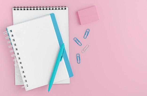 Maquette de cahier vierge blanche, stylo et fournitures de bureau sur espace rose. mise à plat