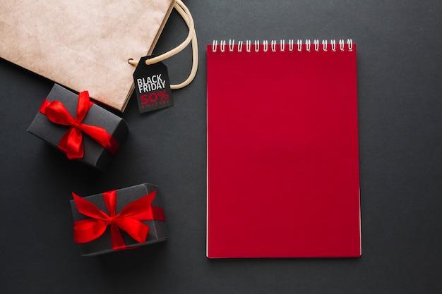 Maquette de carnet rouge avec des cadeaux