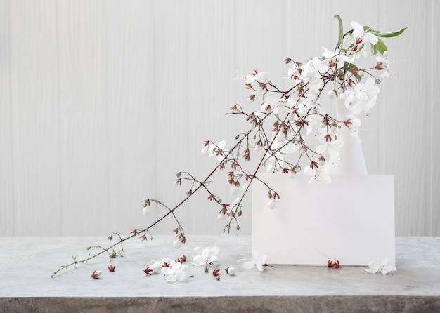 Maquette de carte d'invitation blanche et de belles fleurs de clerodendron hochant la tête dans un vase moderne situé sur une table en béton