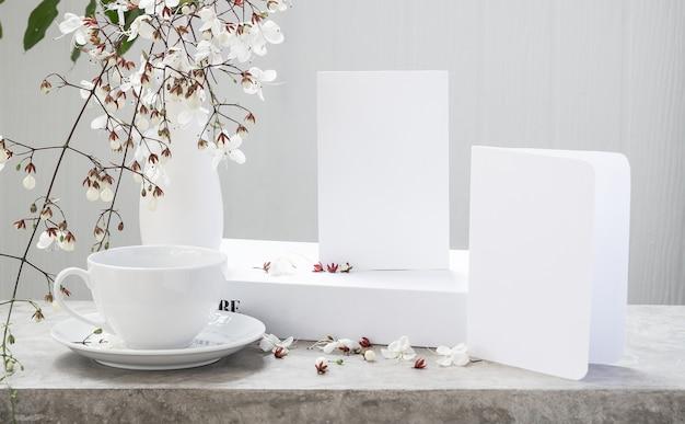 Maquette de carte d'invitation blanche, livre de tasse de café et belles fleurs de clérodendron hochant la tête dans un vase moderne situé sur une table en béton