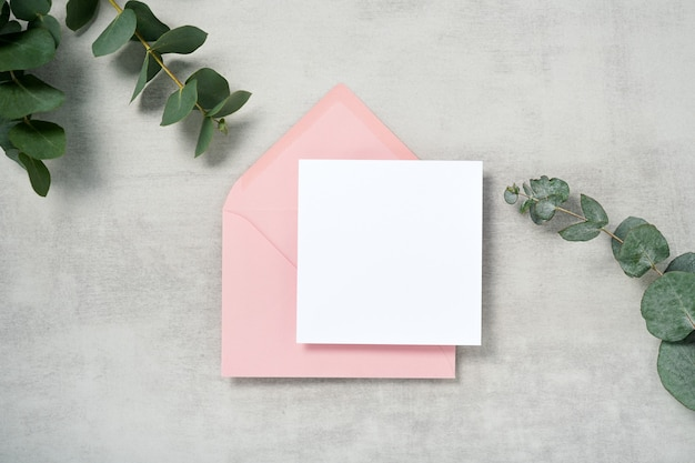 Maquette de carte d'invitation carrée enveloppe rose avec une branche d'eucalyptus