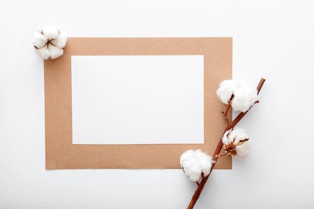 Maquette de carte d'invitation en papier vierge blanche avec branche de fleurs de coton à fleurs sèches à plat. maquette de bureau moderne pour carte de voeux. espace de travail élégant avec maquette blanche dans un cadre de couleur terre.