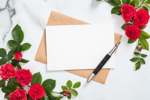 Maquette carte postale avec enveloppe en papier kraft, plume et cadre de fleurs roses