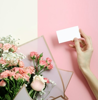 Maquette de carte de voeux dans un bouquet de roses roses, photo vue de dessus