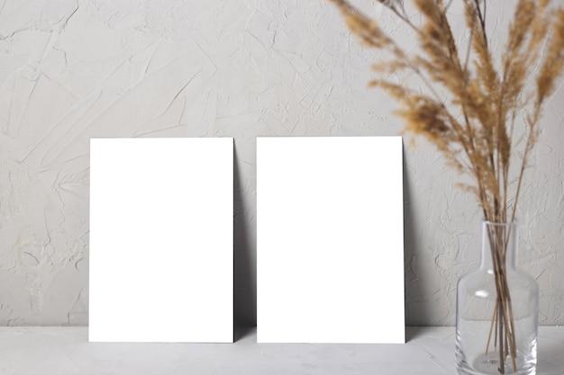 Maquette de carte de voeux sur gris suivant avec bouquet de fleurs séchées