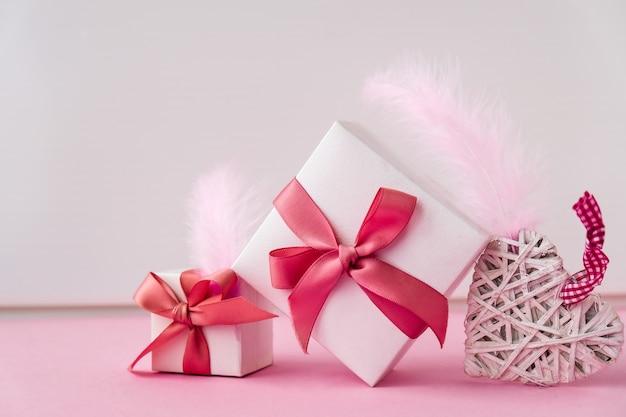 Maquette de carte de voeux joyeuse saint-valentin. coffrets cadeaux et coeurs. espace de copie. plumes roses
