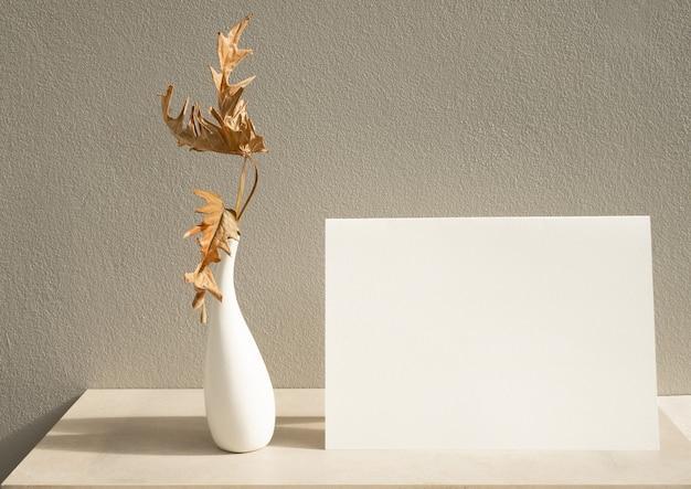 Maquette de cartes blanches d'invitation et de feuilles sèches philodendron exotiques dans un vase moderne sur table avec fond en béton