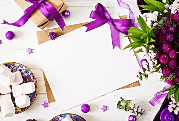 Maquette. cartes et fleurs, coffret cadeau, ruban violet et chiffon posé sur une table blanche.