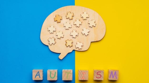 Maquette d'un cerveau humain avec des pièces de puzzle dispersées sur un fond jaune et bleu