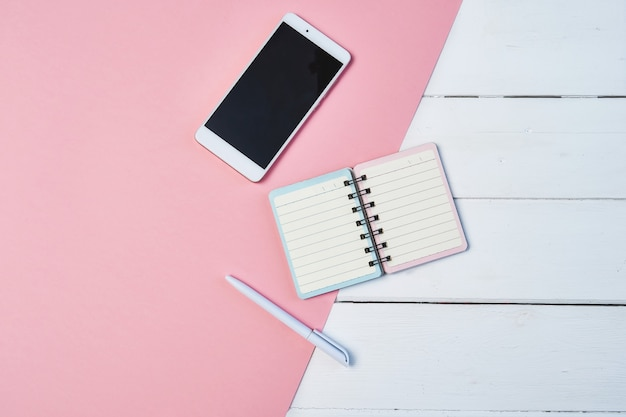 Maquette composition à plat avec smartphone et bloc-notes sur un fond bleu et rose. bureau avec espace de copie