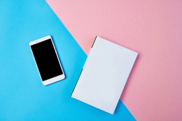 Maquette composition à plat avec smartphone et bloc-notes sur un fond bleu et rose.