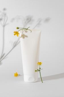 Maquette cosmétique blanche sur fond blanc. concept de minimalisme dans les emballages cosmétiques. tube cosmétique blanc pour crème pour le visage. maquette de concept de beauté.