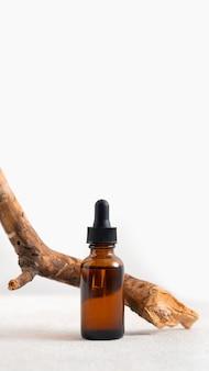 Maquette cosmétique visage sérum bouteille en verre brun avec une pipette sur un fond blanc minimaliste élégant avec écorce d'arbre