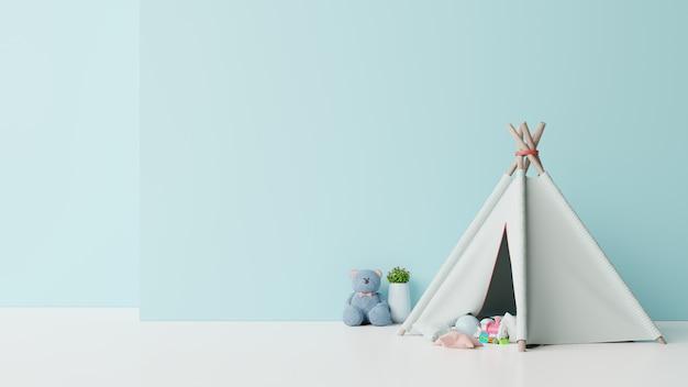 Maquette dans la salle de jeux pour enfants avec une poupée assise sur une tente et une table sur un mur bleu vide.