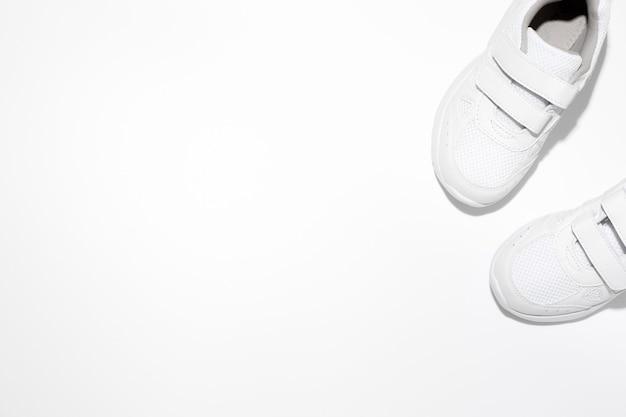 Maquette de deux baskets blanches pour enfants avec fermetures velcro avec espace de copie isolé sur fond blanc...