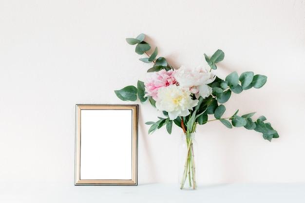 Maquette du cadre avec un bouquet de pivoines et de branches d'eucalyptus