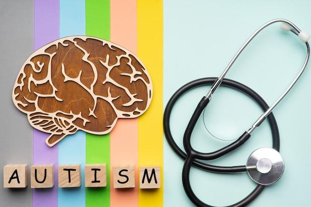 Maquette du cerveau humain avec un stéthoscope sur un fond coloré. six cubes avec l'inscription autisme.