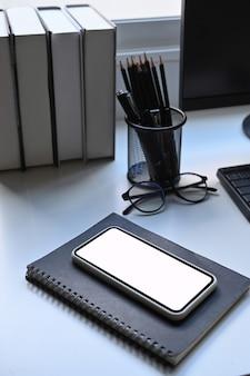 Maquette du téléphone portable, du porte-crayon et des livres sur un tableau blanc.