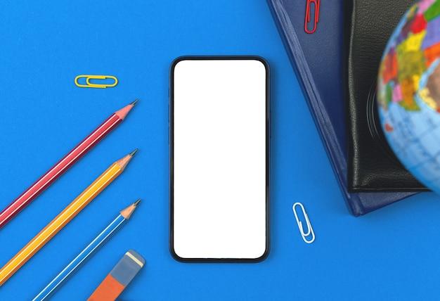 Maquette d'école avec téléphone portable et écran blanc vierge avec espace de copie, table avec crayons, globe et fournitures scolaires, photo de composition vue de dessus