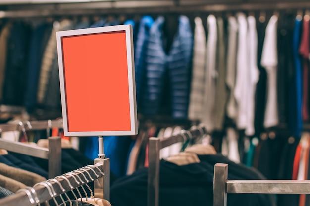 Maquette d'enseigne sur le fond d'un magasin avec des vêtements.