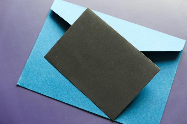 Maquette d'enveloppe avec une carte d'invitation sur la table.