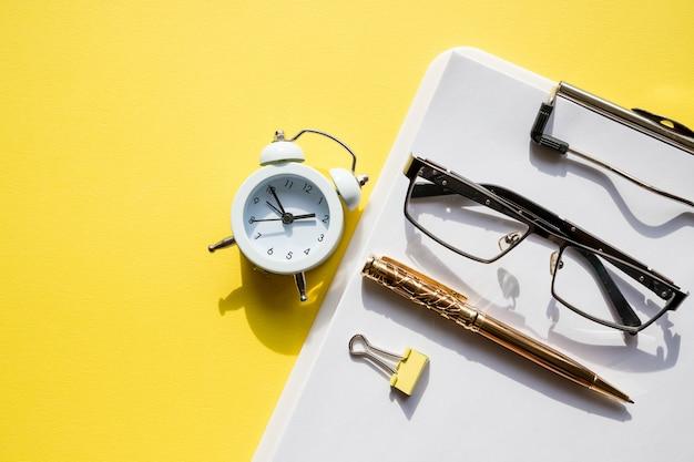 Maquette de l'espace de travail du bureau à domicile avec ordinateur portable, presse-papiers, coton, café, écouteurs, lunettes et accessoires. succès dans le concept d'entreprise, d'emploi et d'éducation. design minimaliste, espace de travail