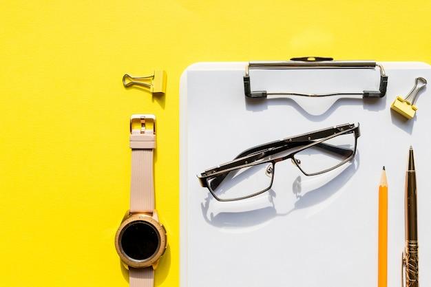 Maquette de l'espace de travail du bureau à domicile avec presse-papiers, montre, lunettes et accessoires. liste de contrôle, papier vide sur mur jaune. concept de bureau, écrivain ou étude modèle pour blog, blogueur, entreprise