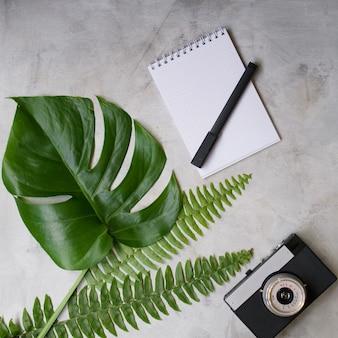 Maquette d'espace de travail avec feuille de palmier tropical, cahier, appareil photo, stylo, carte et tasse à café