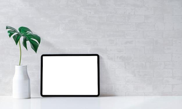 Maquette de l'espace de travail avec une tablette à écran vierge et un vase en céramique sur une table blanche.