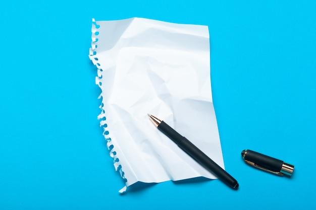 Maquette d'espace de travail vue de dessus sur bleu avec bloc-notes, stylo