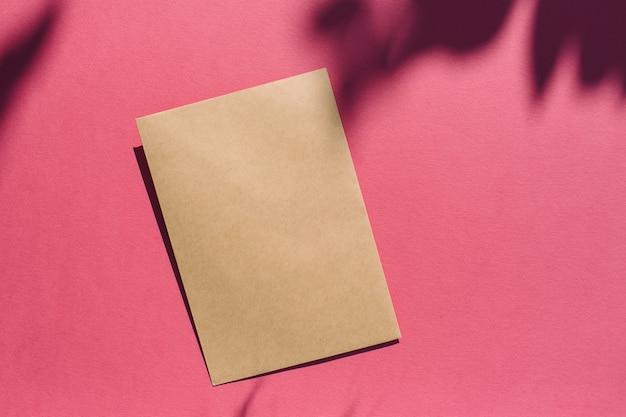Maquette d'été à la mode faite avec une carte vierge verticale, papier kraft sur fond ensoleillé rose vif. concept d'ombre d'été minimal avec espace de copie créative. mise à plat, vue de dessus, mise en page