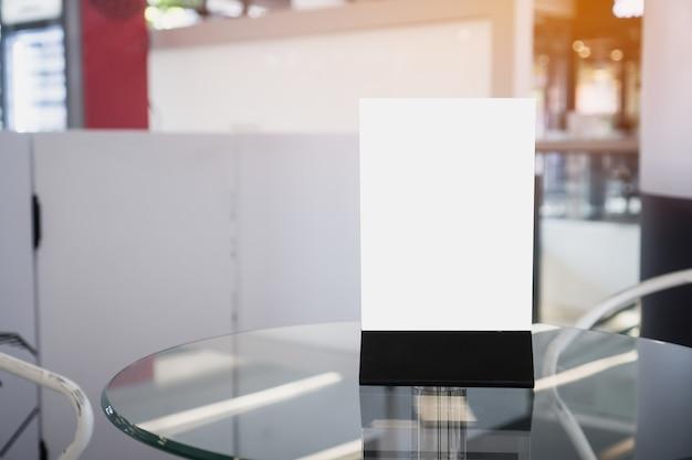 Maquette étiquette blanche pour cadre de menu vierge dans le café du restaurant. tenez les feuilles de livret sur la carte de tente en papier sur la cafétéria de la table pour afficher votre produit arrière-plan flou insérez le texte du client. espace pour envoyer des sms