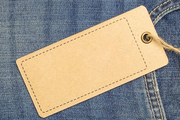 Maquette d'étiquette de prix sur un jean bleu à partir de papier recyclé.