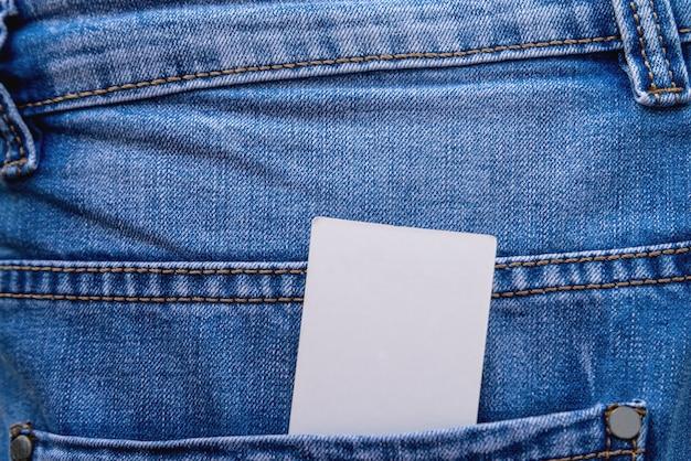Maquette d'une étiquette vierge en papier dans la poche sur un gros plan de jeans bleus.
