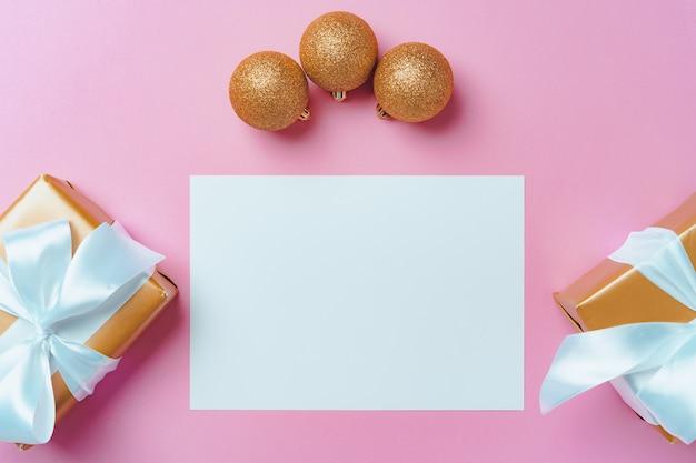 Maquette de fête de noël avec page blanche, cadeaux emballés et boules sur rose