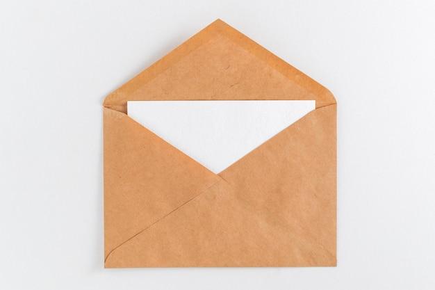 Maquette feuille blanche blanche dans une enveloppe sur fond blanc.