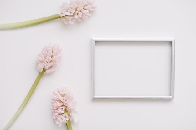 Maquette avec des fleurs roses et un cadre photo vierge