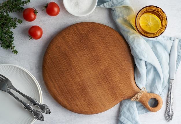 Maquette de fond de nourriture avec planche à découper en bois ronde sur fond de béton gris neutre pastel. vue de dessus, copiez l'espace. menu, recette, maquette.