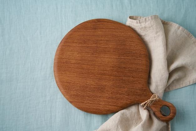Maquette de fond de nourriture avec planche à découper en bois ronde sur fond de nappe textile en lin bleu