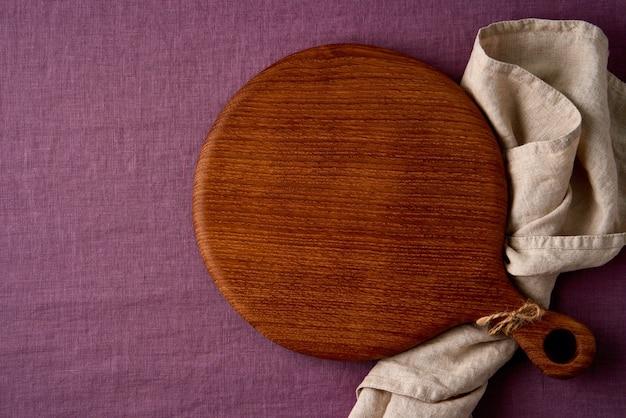 Maquette de fond de nourriture avec planche à découper en bois ronde sur lin bleuet, textile de couleur rouge