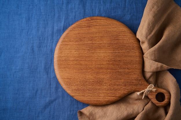 Maquette de fond de nourriture avec planche à découper en bois ronde sur nappe textile en lin bleu vif