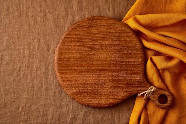 Maquette de fond de nourriture avec planche à découper en bois ronde sur nappe textile en lin marron jaune